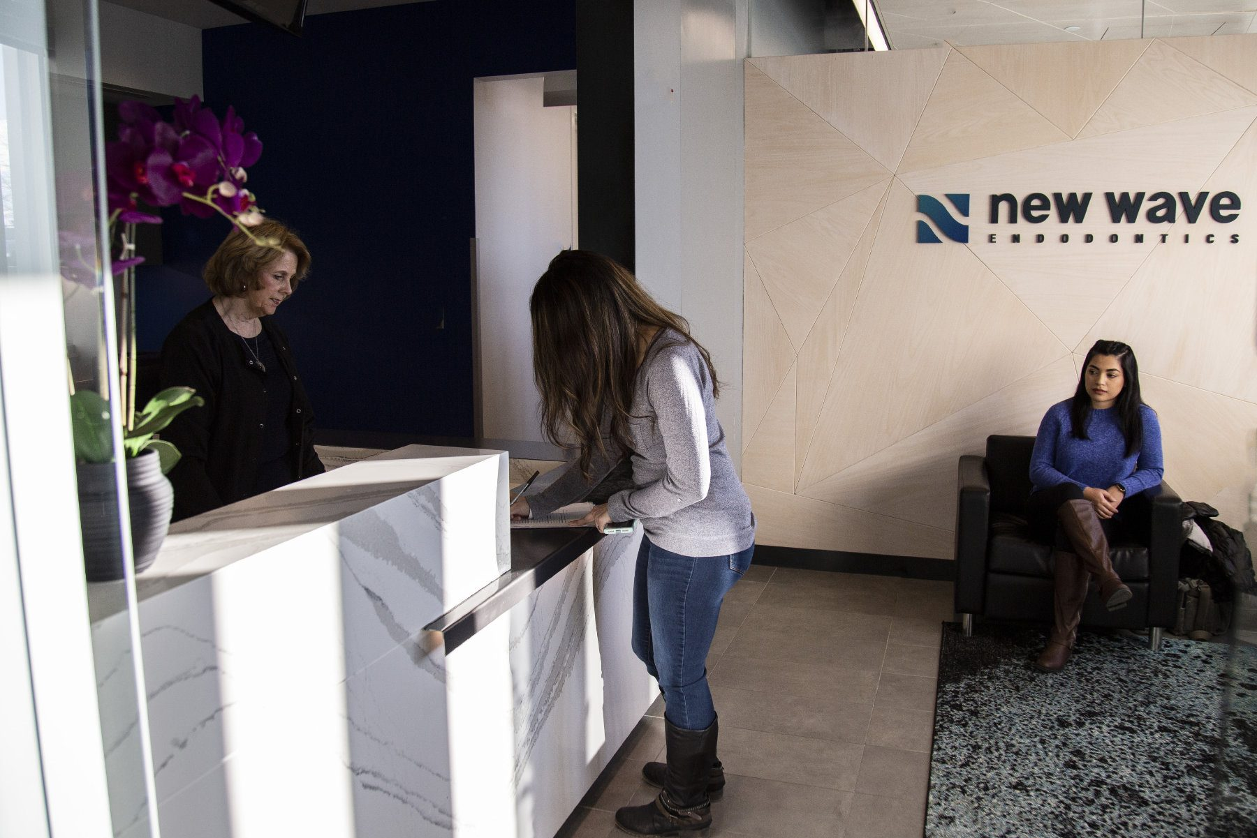 a patient signs in with a receptionist in front of a New Wave Endodontics logo