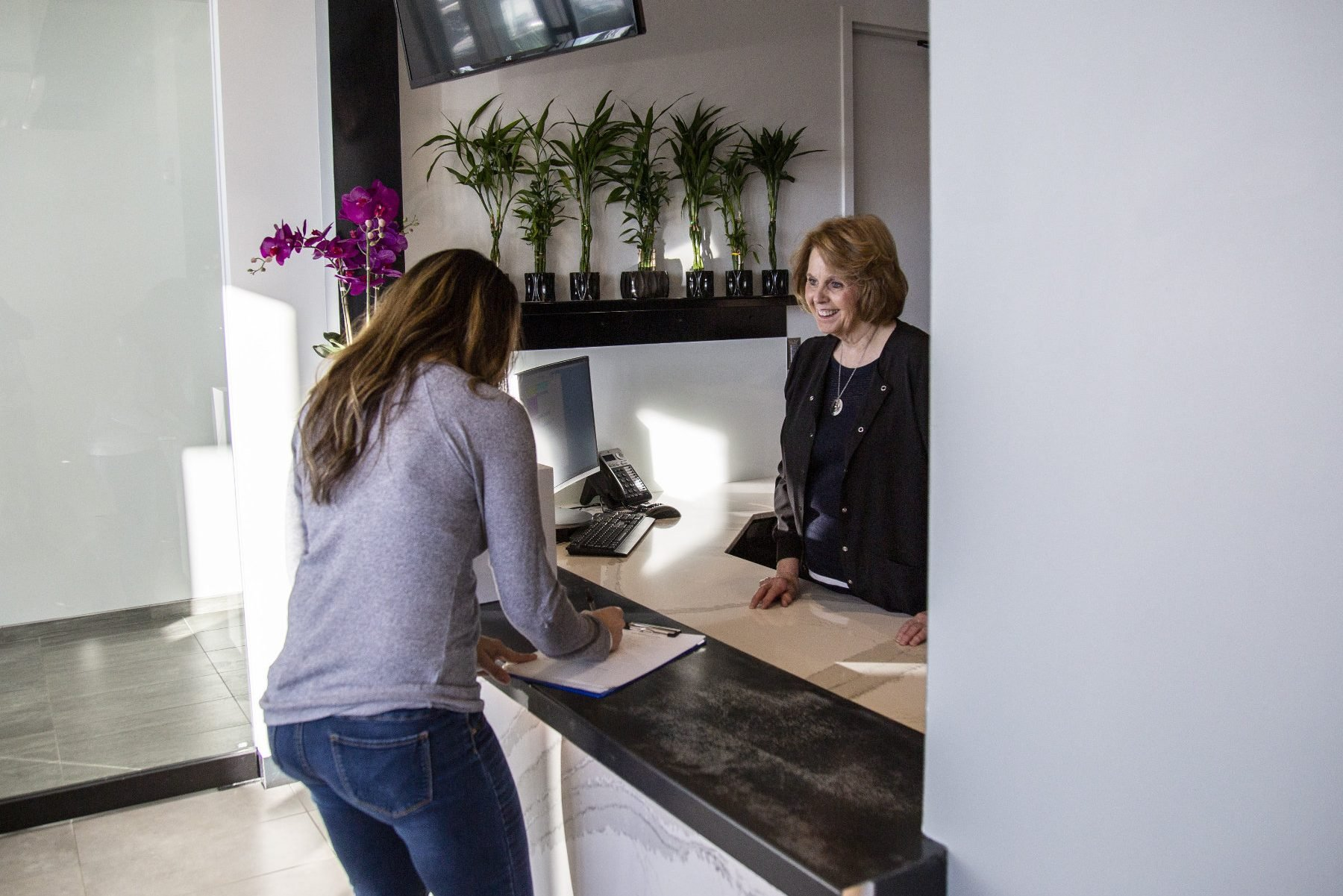a patient signs in with a receptionist
